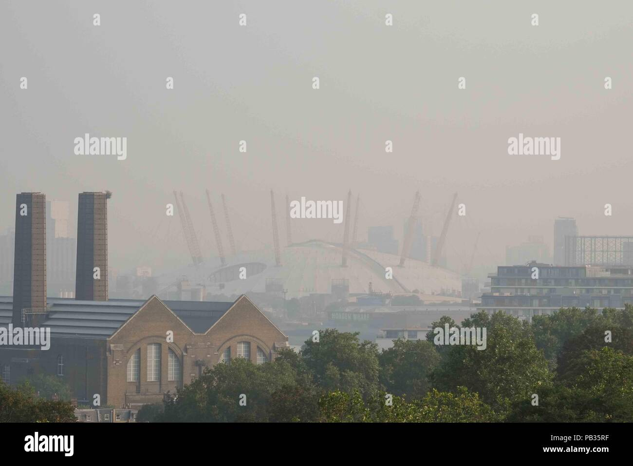 London 26th July 2018:  Early morning smog hangs over the O2 arena, seen from Greenwich Park  as Mayor Sadiq Khan triggers a high pollution alert for London amid concerns over extremeley high tempertures. The capital is expected to reach a temperture of 36C today. Credit : Claire Doherty/Alamy Live News - Stock Image