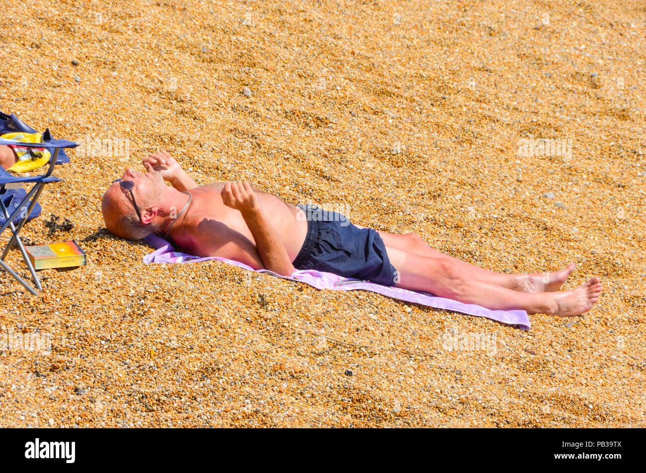 West Bay, Dorset, UK.  26th July 2018. UK Weather.  A sunbather on the beach at the seaside resort of West Bay in Dorset enjoying the hot sunshine as the heatwave continues.  Picture Credit: Graham Hunt/Alamy Live News - Stock Image