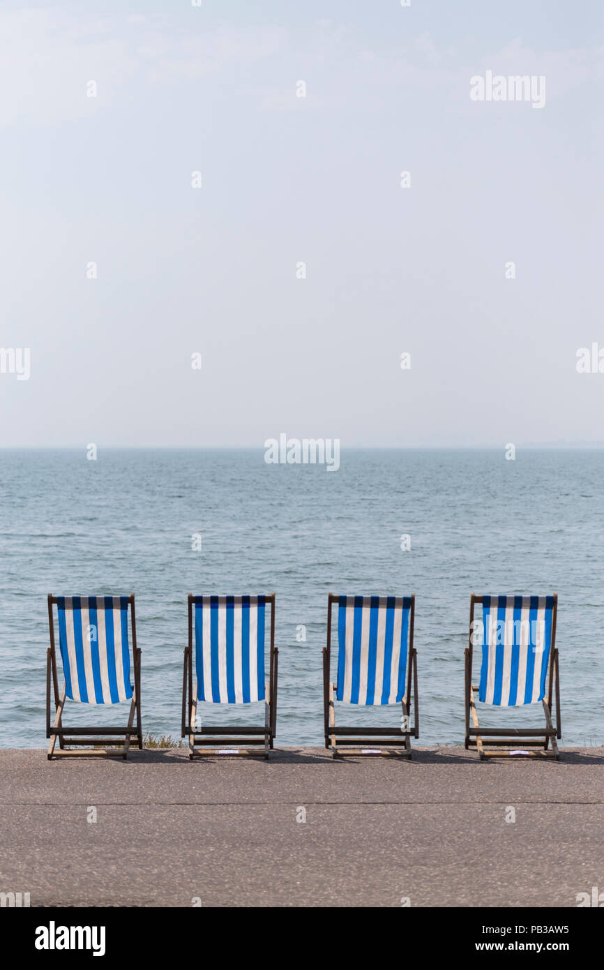 Four Unoccupied Traditional Style Deckchairs on Seafront at Westcliff-on-Sea During Heatwave of July 2018 Stock Photo