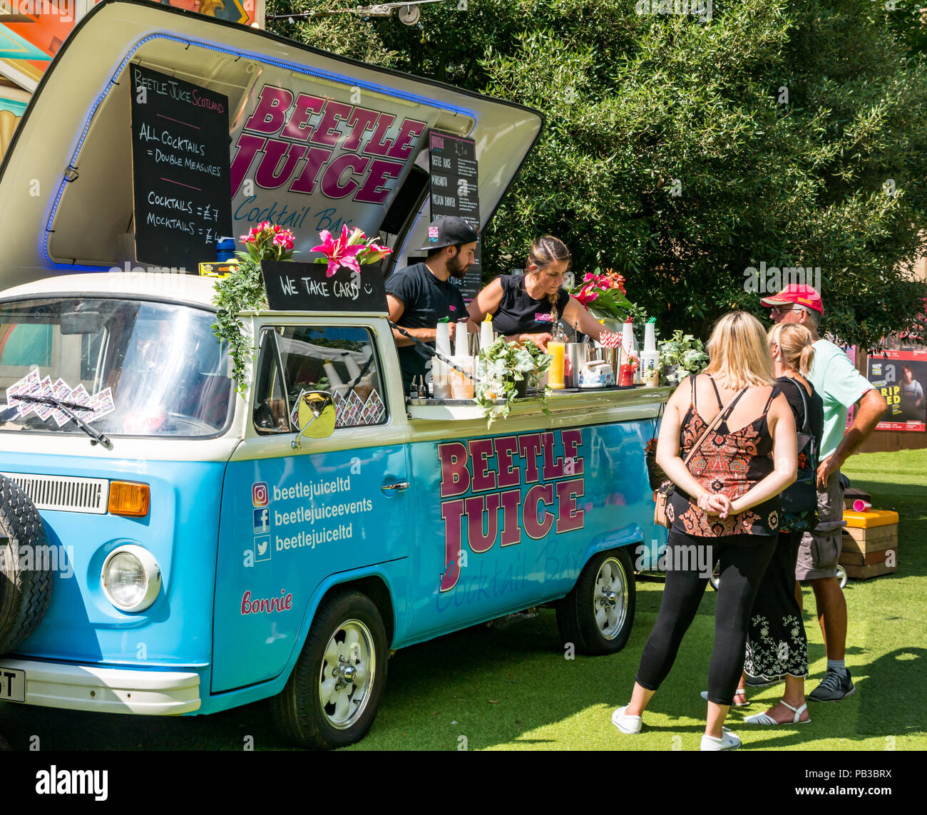Edinburgh, UK. 26th July 2018. Edinburgh Food Festival 2018 in George Square Gardens, Edinburgh, Scotland, United Kingdom. There are food stalls with over 20 local food and drink producers in the free outdoor event. Customers at the Beetle Juice VW cocktail van bar - Stock Image