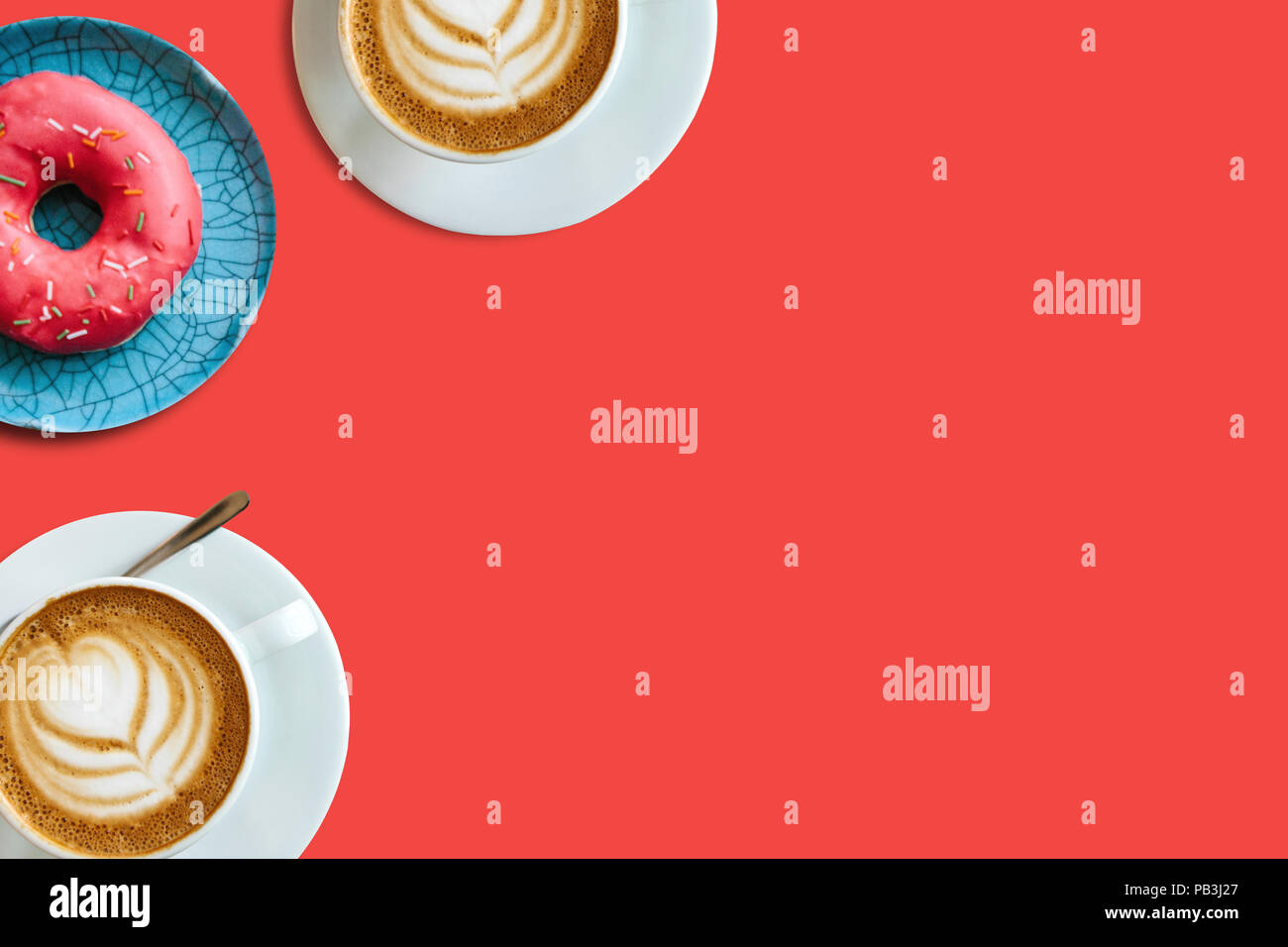 Top view. Two cups of fragrant delicious coffee cappuccino and a number of donut on a red background. Nearby place for text. - Stock Image