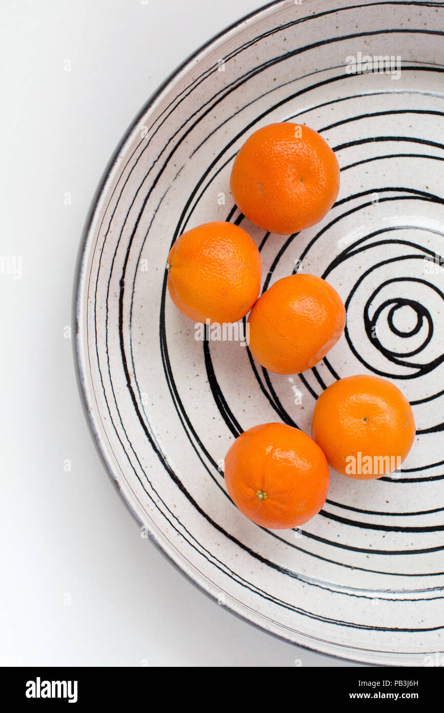Five easy peel tangerines in a large fruit bowl with a spiral pattern on a white background - Stock Image