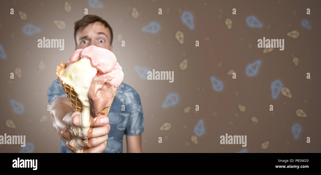 Man with a melting ice cream cone in his hand - Stock Image