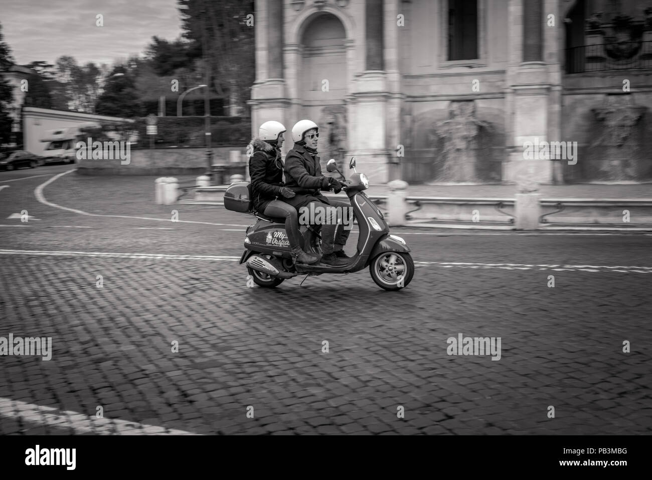 Panning photograph of a couple riding a Vespa scooter in front of Fontana dell'Acqua Paola in Rome - Stock Image