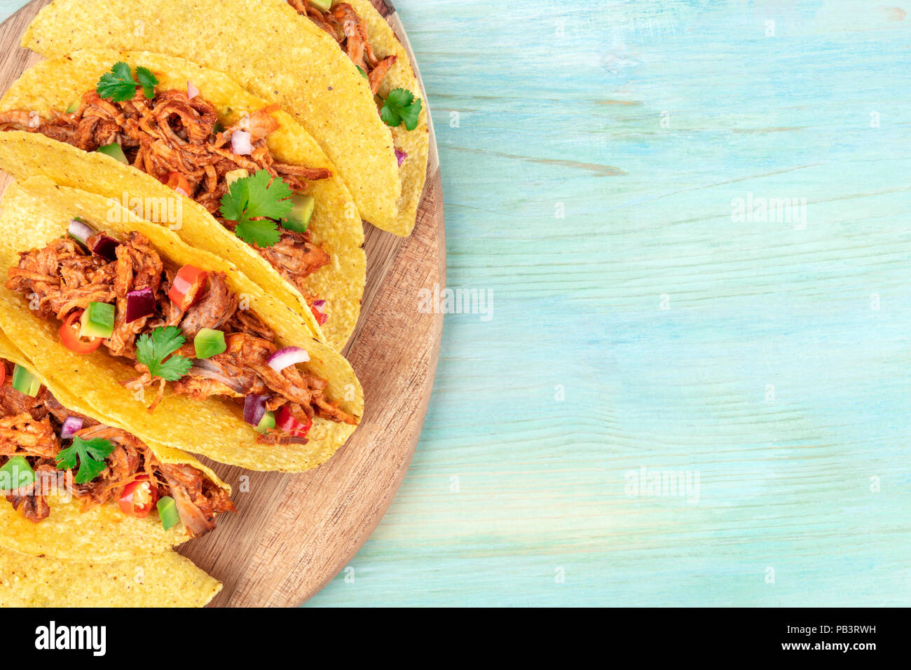 Overhead closeup photo of Mexican tacos with pulled pork, avocado, chili peppers, cilantro, with place for text - Stock Image