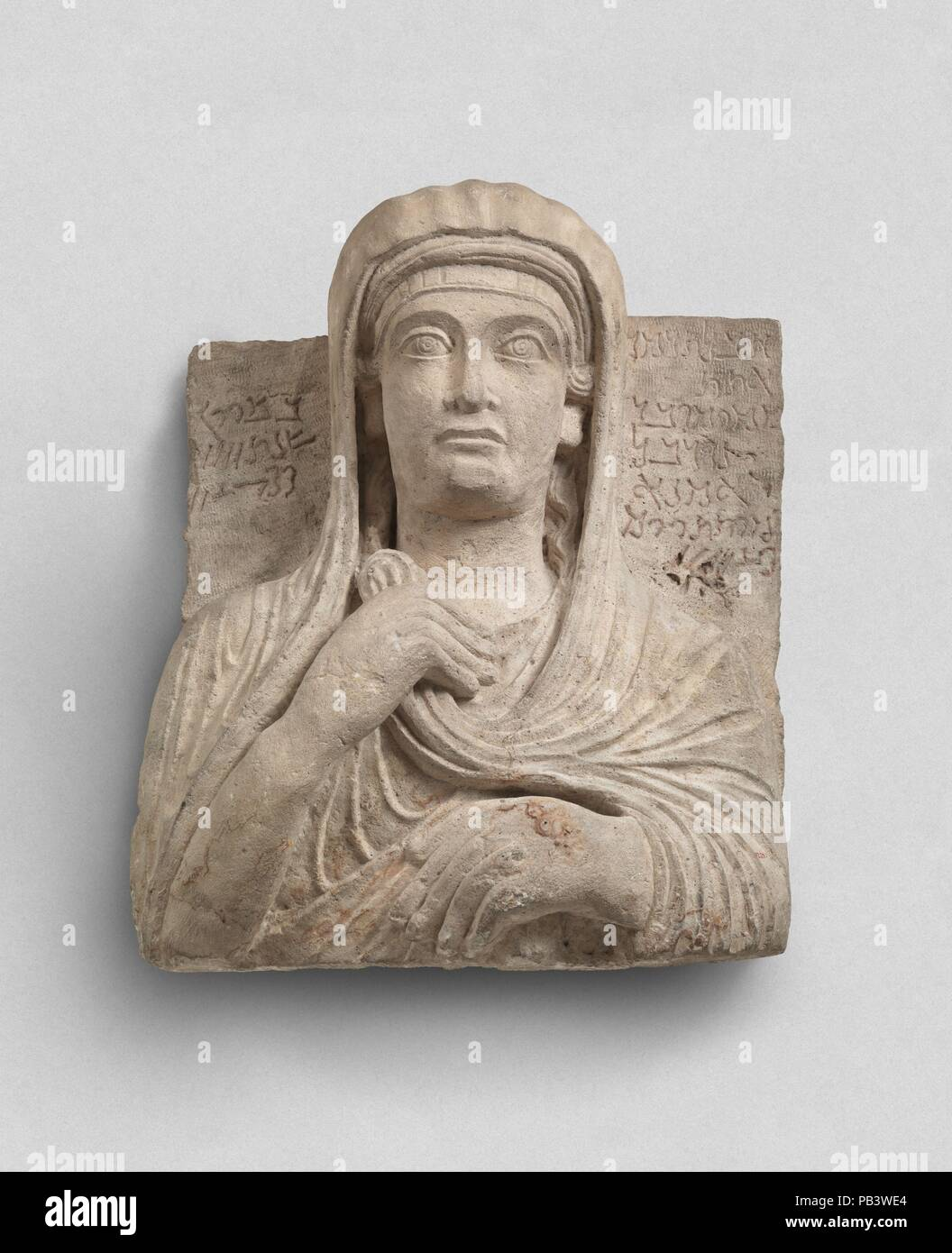 Funerary relief. Dimensions: 20.39 x 17.36 in. (51.79 x 44.09 cm). Date: ca. 148.  Inscription:  (at right)   1 Alas! Tadmur,   2 wife of   3 Mokimu, son of   4 Nurbel,   5 the craftsman.   6 Died the   7 29th day   (at left)   8 of Siwan,   9 in the year   10 459.  Transliteration:  1 hbl tdmr  2 ?tt  3 mqymw br  4 nwrbl  5 ?mn?  6 mytt yw!m  7 20+5+4  8 bsyw!n  9 snt 4.[100]  10 +40+10+5+2  This relief is a type of funerary monument characteristic of the prosperous caravan city of Palmyra during the first three centuries A.D. Reliefs with a representation of the deceased and a short identify - Stock Image