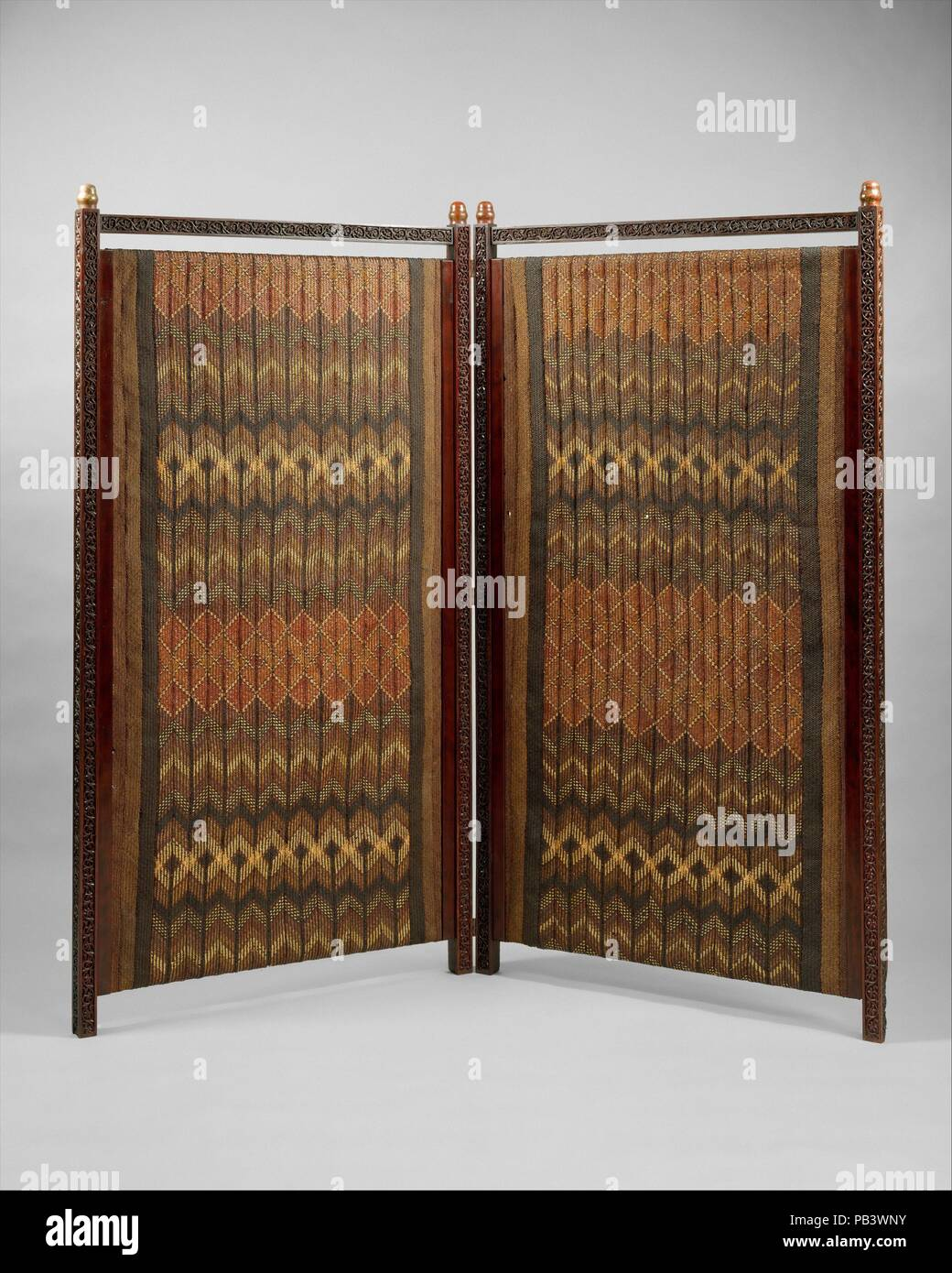 Screen. Culture: American. Designer: Designed by Lockwood de Forest (American, New York 1850-1932 Santa Barbara, California). Dimensions: 65 x 69 3/4 x 1 3/4 in. (165.1 x 177.2 x 4.4 cm). Date: ca. 1881-90.  With its carved teak frame, vividly patterned plaited matting, and Japanese lacquer and mixed-metal finials, this unusual screen epitomizes the 1880s fascination with exotic styles and materials. The screen's designer, Lockwood de Forest, who was trained as a painter, did much to foster popular taste for such exoticism in decorative arts and architecture during the late nineteenth century. Stock Photo