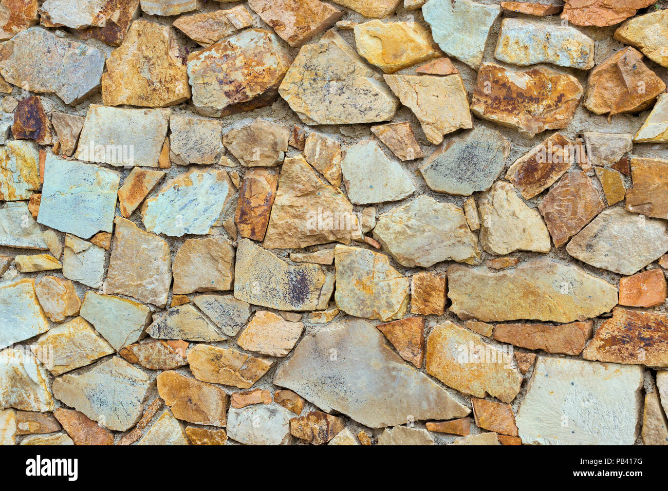 lovely Decorative Stone Wall Part - 7: Decorative stone wall, pieces of rock bonded with cement. Cobble texture  with cracks. Mountain of castle San Juan. Spanish beach resort Blanes in  summ