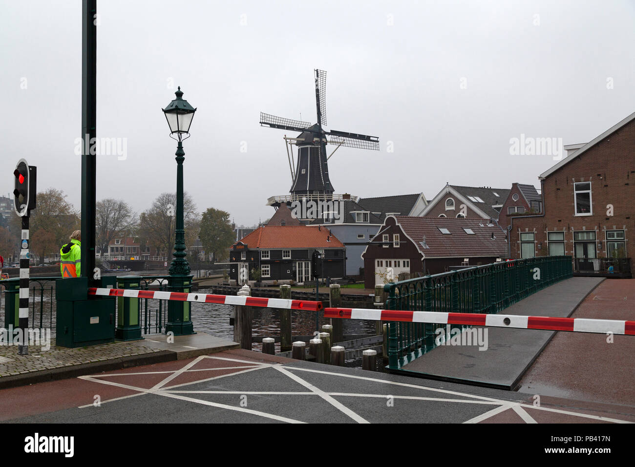 A barrier and red light signify the opening of a bridge over the River Spaarne in Haarlem, the Netherlands. The De Adriaan windmill (Molen de Adriaan) Stock Photo