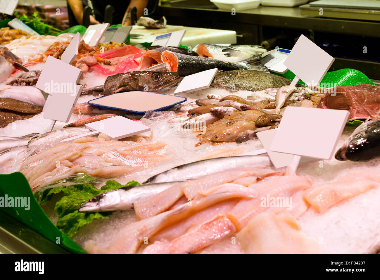 Fresh fish, seafood and sea delicacies on ice countertop in food hypermarket. Chilled fish fillet and oceanic shellfish. Costa Brava, Catalonia, Blane - Stock Image