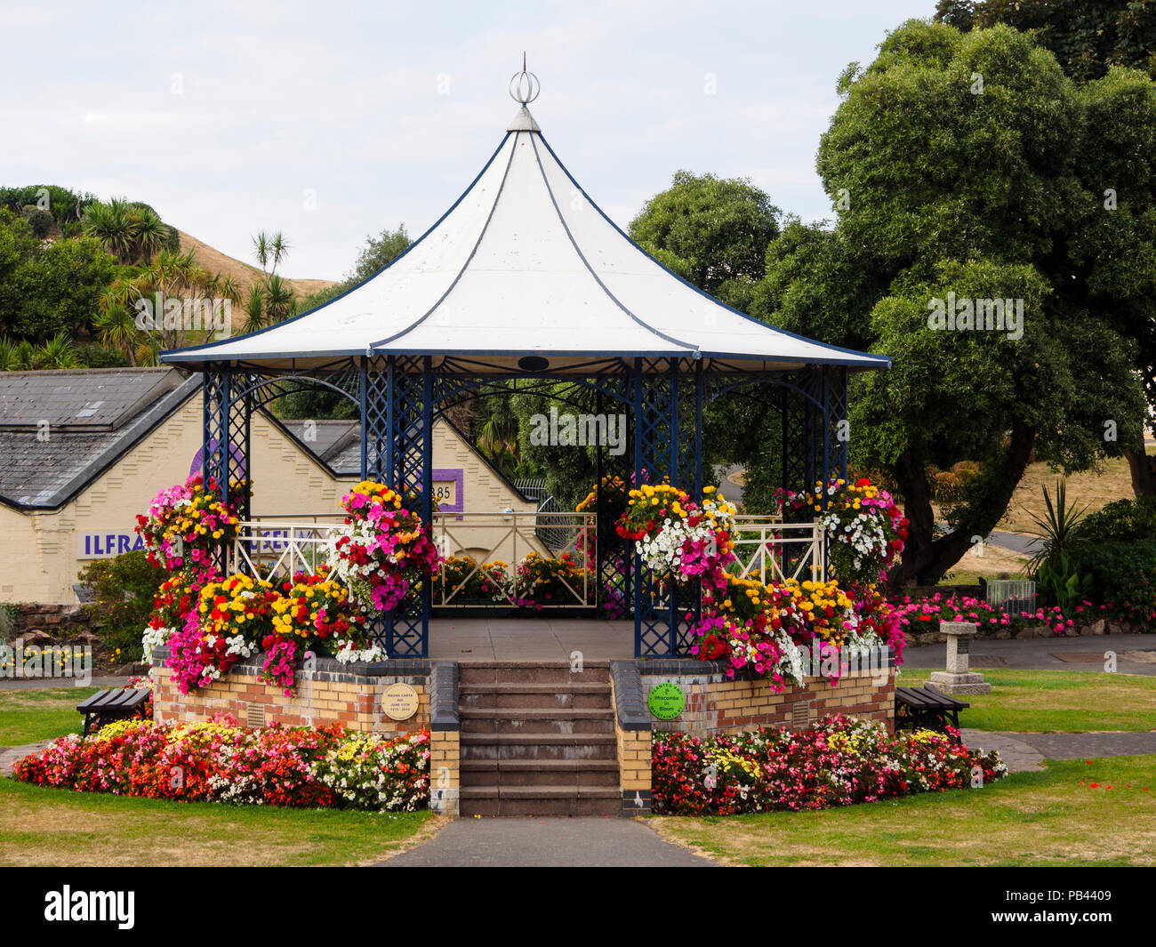Summer bedding flowers bedeck the Victorian bandstand in Runnymede Gardens, Ilfracombe, Devon, UK Stock Photo