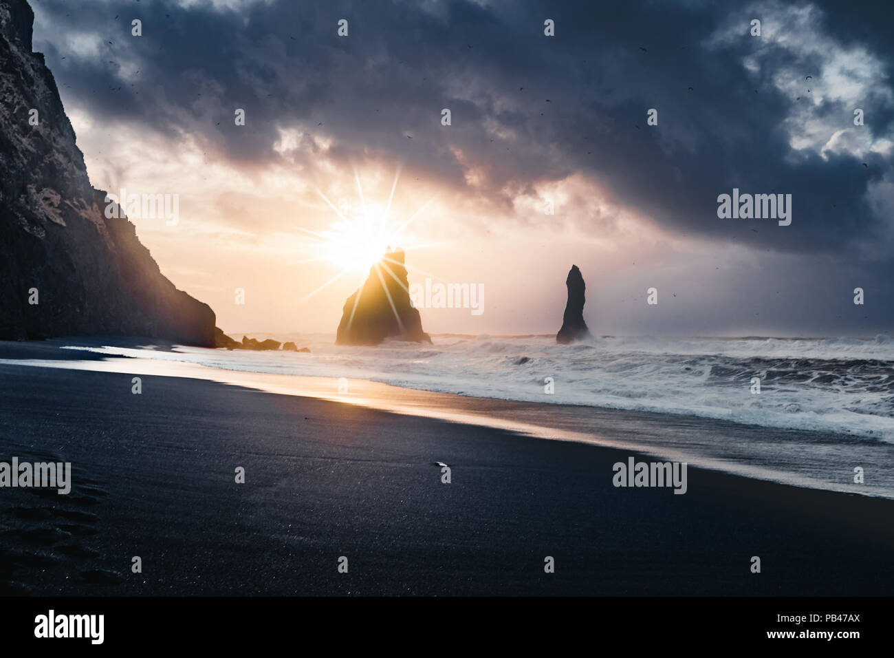Sunrise at famous Black Sand Beach Reynisfjara in Iceland. Windy Morning. Ocean Waves. Colorful Sky. Morning Sunset. - Stock Image