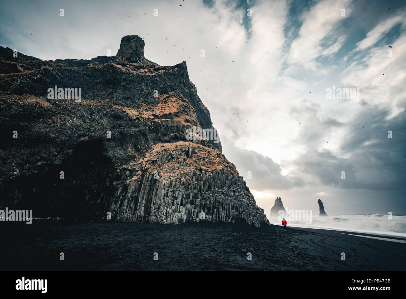 The black sand beach of Reynisfjara and the mount Reynisfjall, Iceland. Windy Morning. Ocean Waves. Colorful Sky. Morning Sunset. - Stock Image
