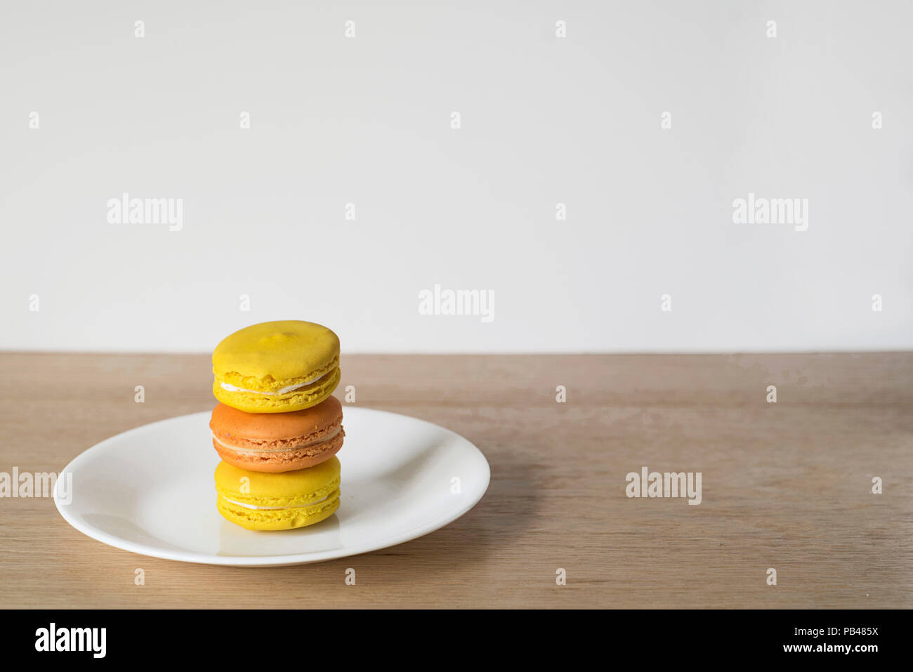 Wide Shot of Orange and Yellow Macaron Tower on a White Plate, Wood Counter, and Light Background - Stock Image