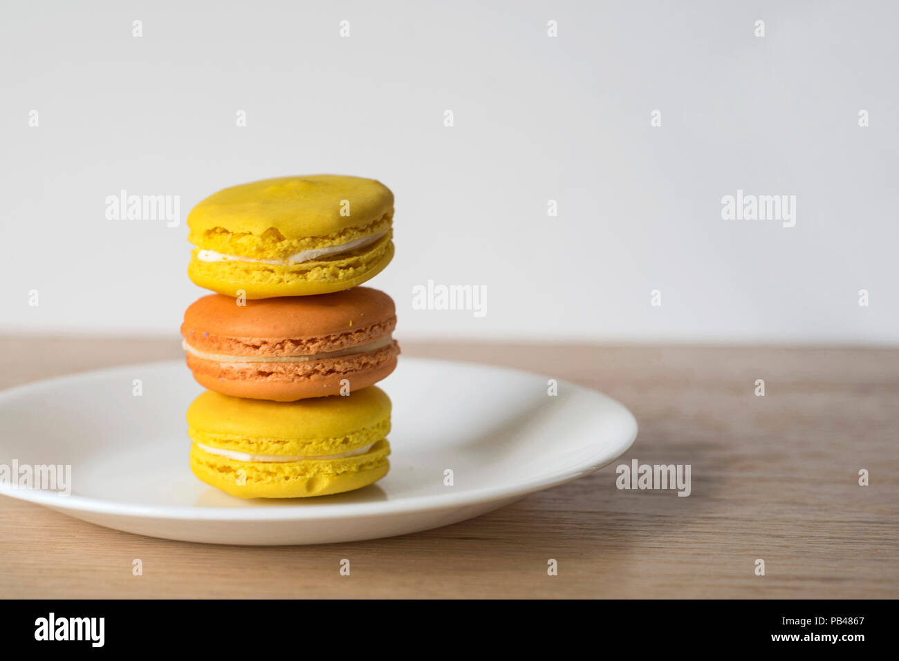 Close-up with the Warm Colors of Yellow and Orange Macaroons Stacked Up - Stock Image
