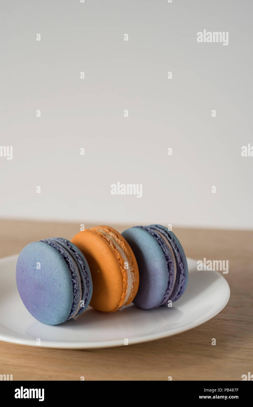 Trio of Two-Color Macarons Standing on a Plate for Dessert - Stock Image