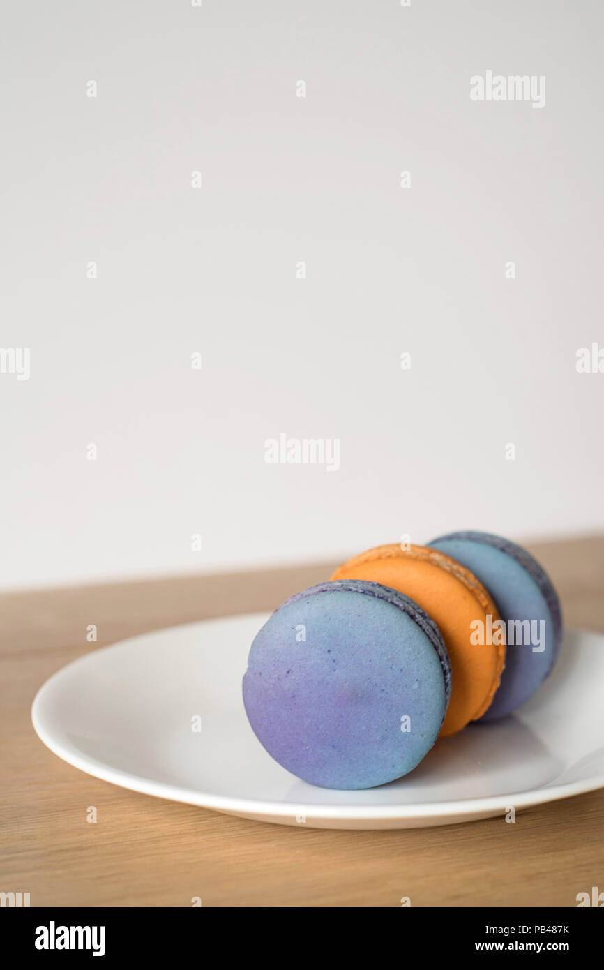 Three Orange and Blue Macarons Sitting on Their Sides on a Plate - Vertical - Stock Image