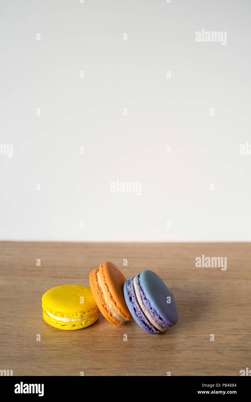 A few macaroons sitting on a table waiting for someone to eat them - Stock Image