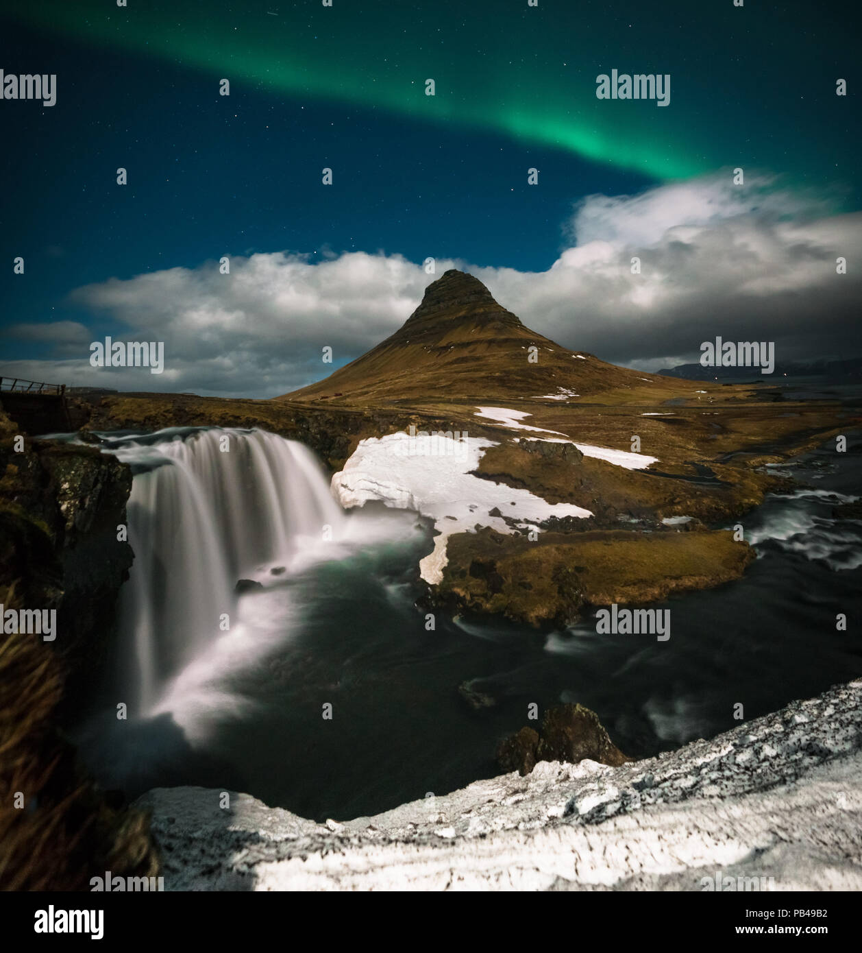 Northern lights aurora borealis appear over Mount Kirkjufell in Iceland. - Stock Image