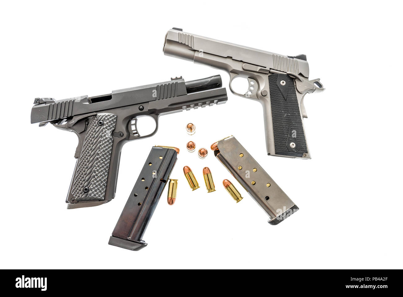 A pair of 1911s with clips and ammunition on an isolated background - Stock Image
