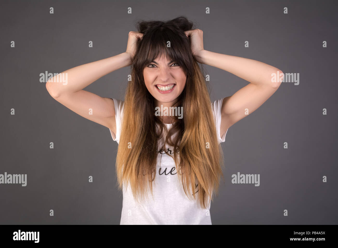 A young woman is shouting loudly. The wicked girl is tearing her hair. - Stock Image