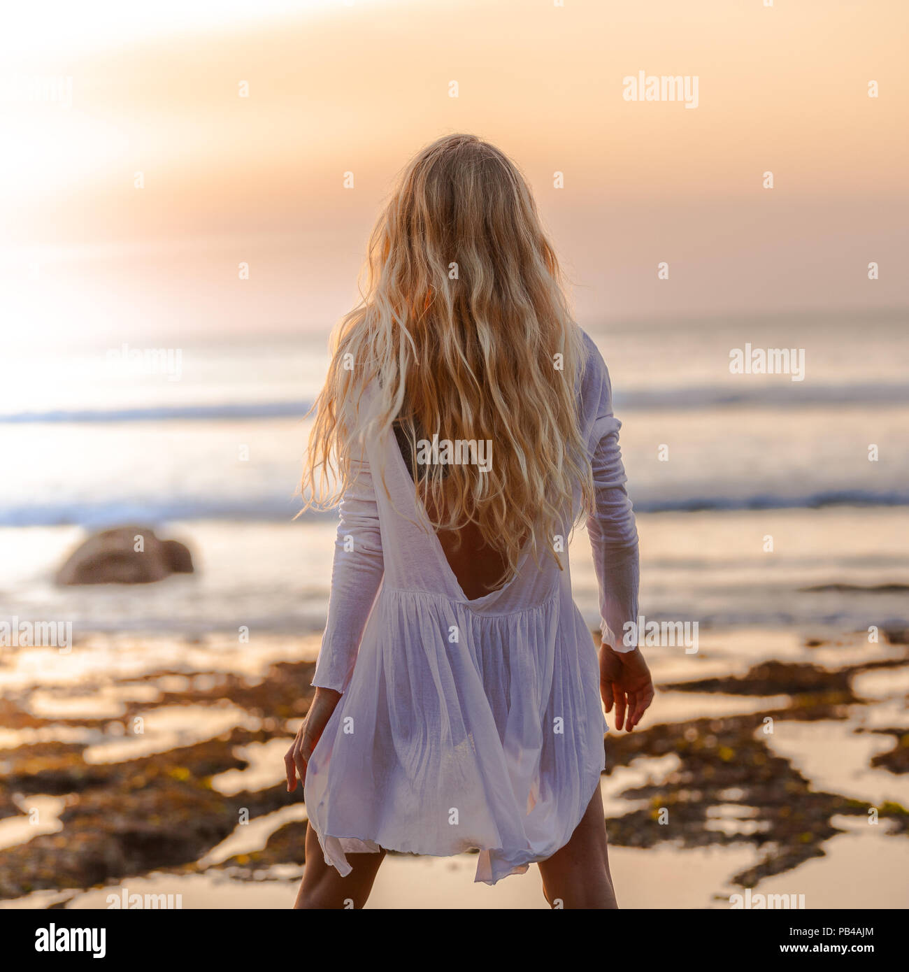 Beautiful blonde girl with long hair in short white dress looking at sunset on the beach in Bali, Indonesia, from behind standing - Stock Image