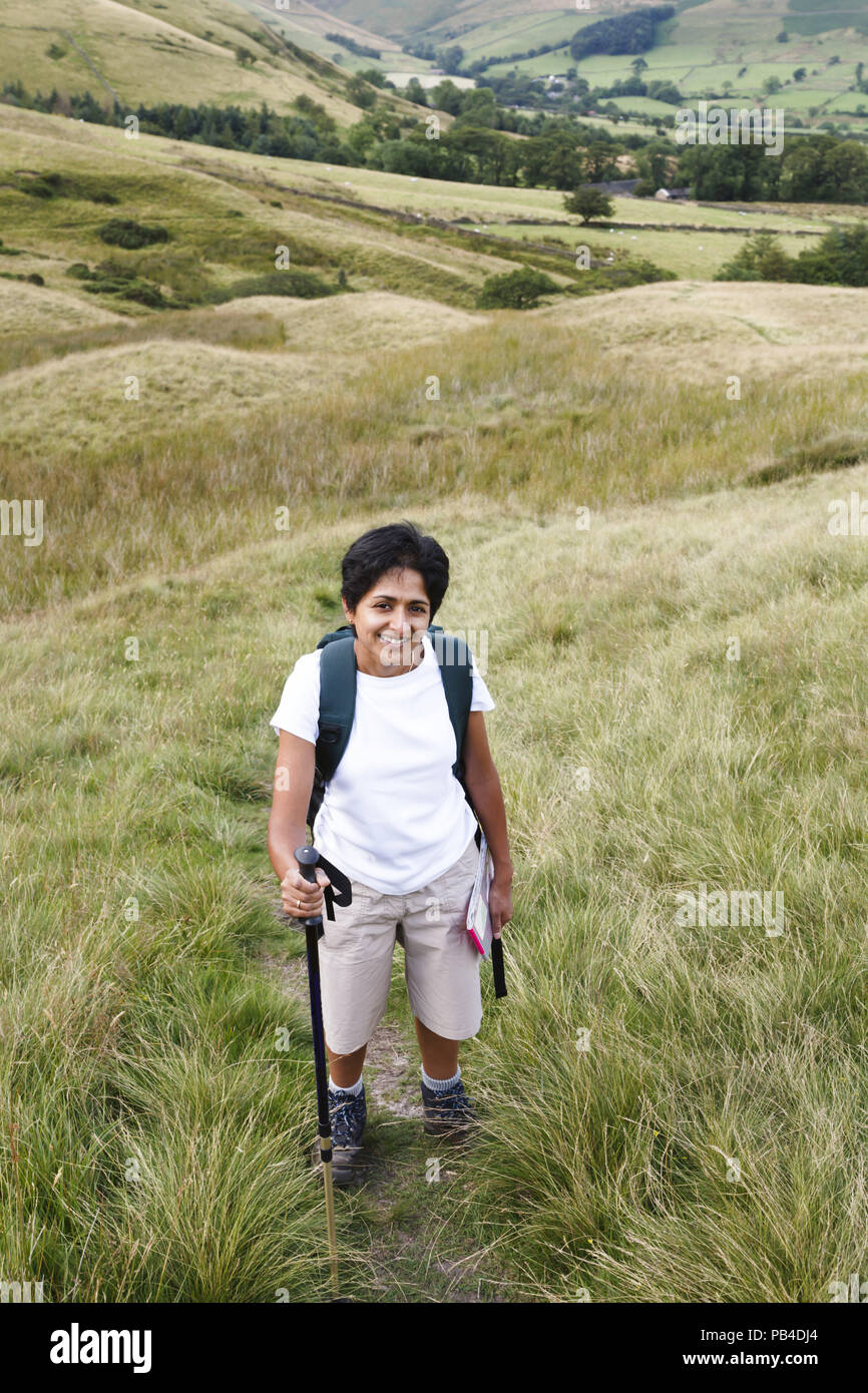 An Indian Asian woman hikes in British countryside - Stock Image