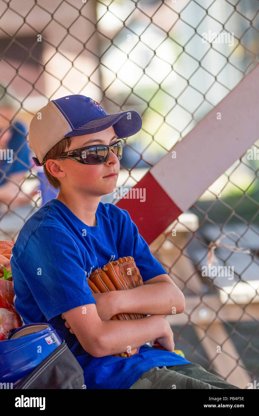 12 Year old boy, holding glove, looking thoughtfull, close up, wearing hat, blue jersey and red shoes, sunglasses. Model Relese #105 - Stock Image