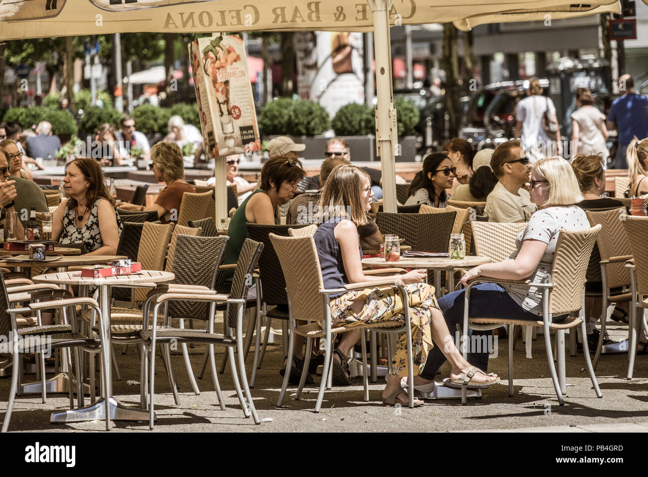 Wolfsburg, Lower-Saxony, Ger,any, July 1st 2018: Cafe occupied by many people in the pedestrian zone during a city festival Stock Photo