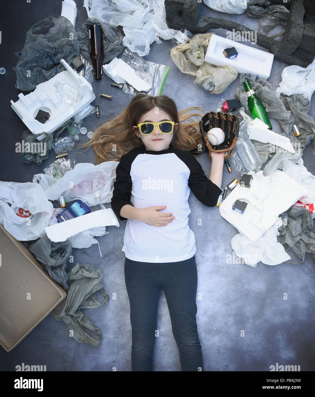 A young child is holding a baseball with garbage waste like plastic bags and non biodegradable products around her for a recycle clean energy concept  - Stock Image