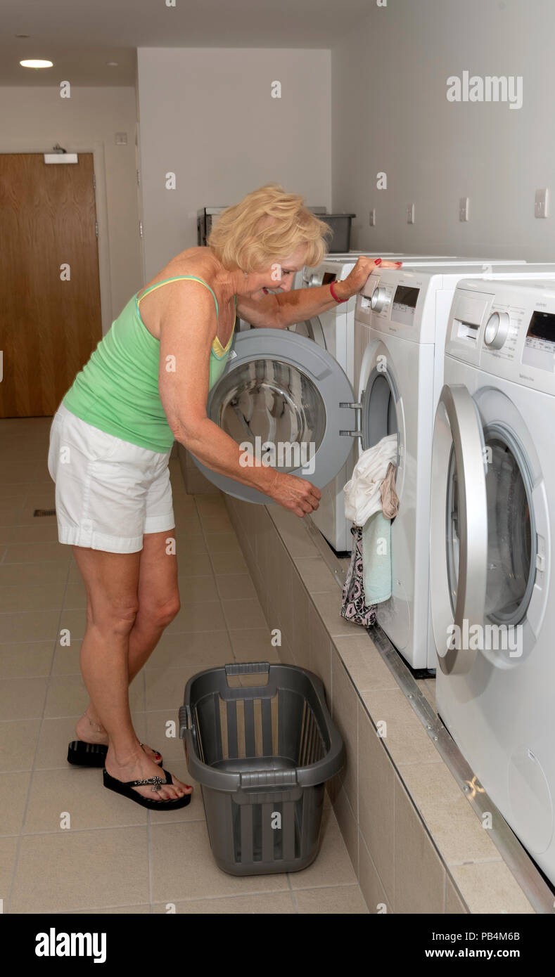 Woman using a washing machine in a laundry room, Stock Photo