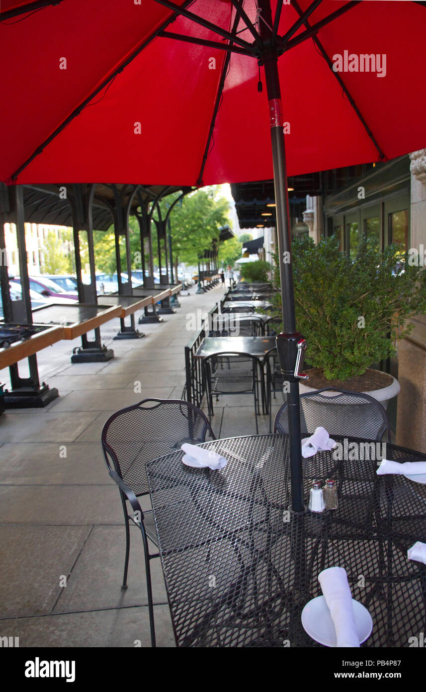 ASHEVILLE, NC, USA - JUNE 29, 2017:Outdoor cafe tables and chairs and cars  and and vendor booths line the sidewalk on the outside of the Grove Arcade - ASHEVILLE, NC, USA - JUNE 29, 2017:Outdoor Cafe Tables And Chairs