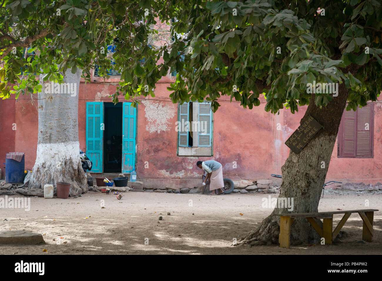 A woman sweeping the outside of her home on Goree island. Senegal - Stock Image