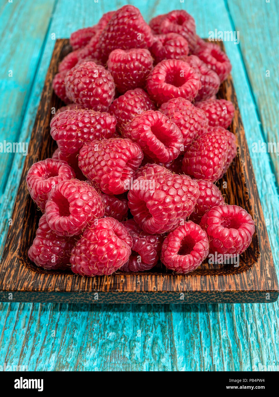Fresh raspberry in a wooden plate - Stock Image
