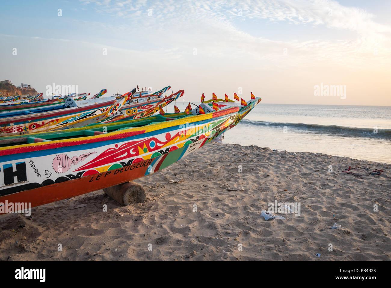 Colourful boats on the beach at Toubab Dialao, Senegal - Stock Image