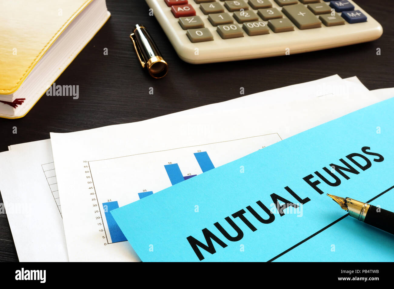 Financial documents about mutual funds on a desk. - Stock Image