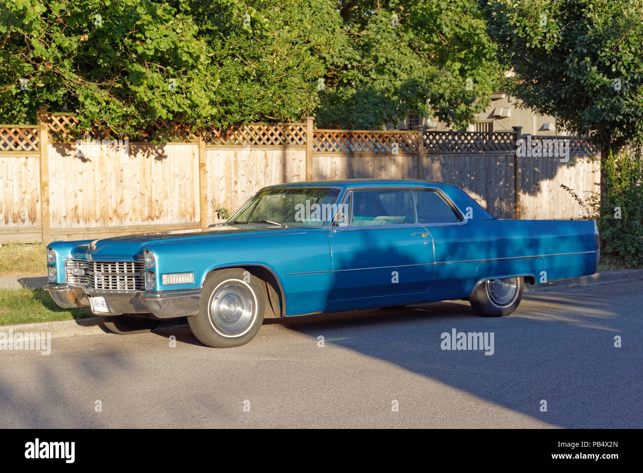Vintage blue 1966 Coupe de Ville Cadillac two door sedan parked on a residential street in Vancouver, BC, Canada - Stock Image