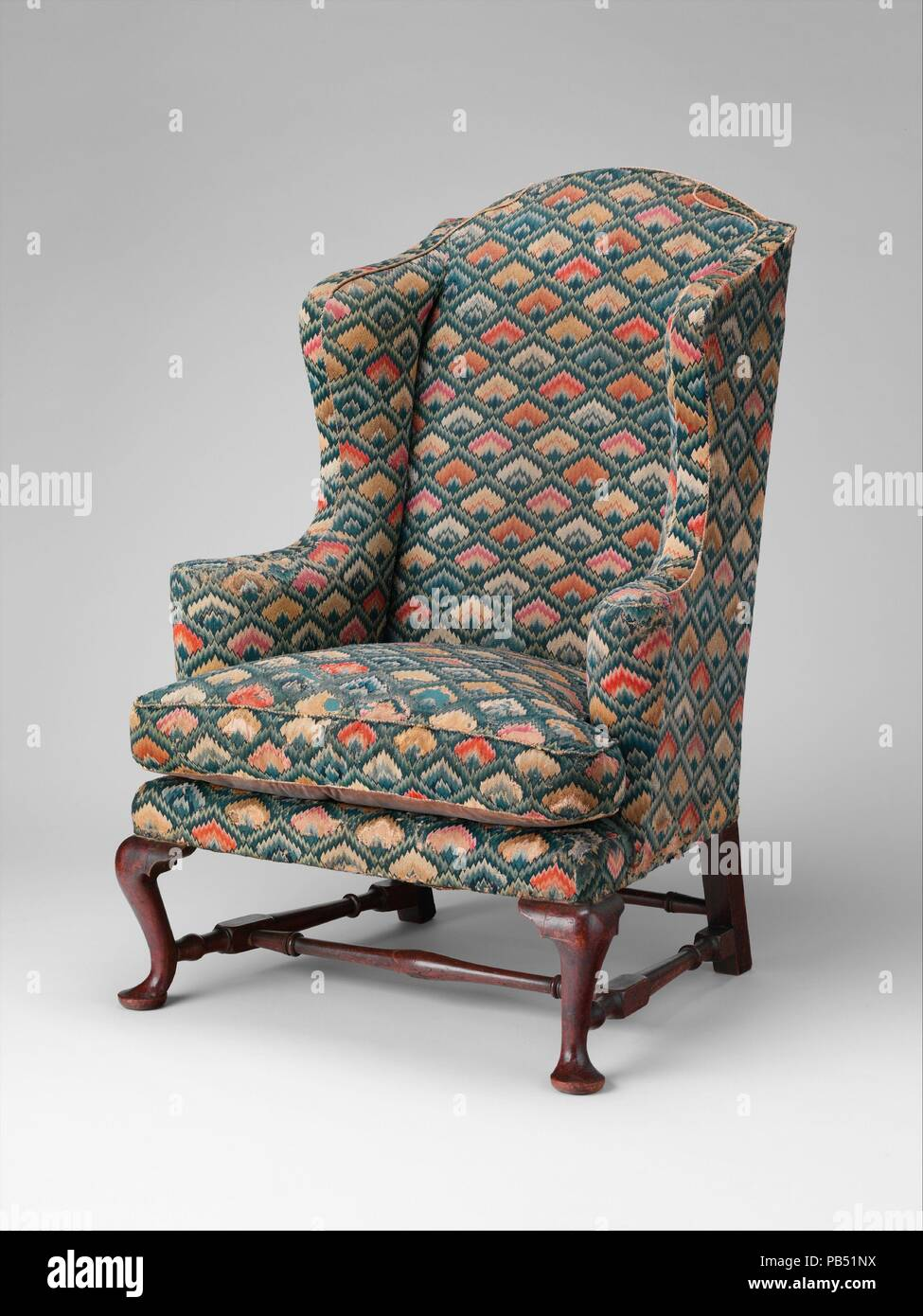 Easy Chair. Culture: American. Dimensions: 46 3/8 x 32 3/8 x 25 7/8 in. (117.8 x 82.2 x 65.7 cm). Maker: Caleb Gardner (died 1761). Date: 1758.  Eighteenth-century easy chairs--heavily  padded, with thick down-filled cushions, and with wings to rest one's head against and keep drafts away--were often reserved for the elderly or the infirm. This New England example is remarkable for its elaborate upholstery and intact condition. The front is covered with Irish stitch needlework and the back with a needlework landscape scene. The seams are covered with silk tape. The frame is inscribed ' Made by - Stock Image