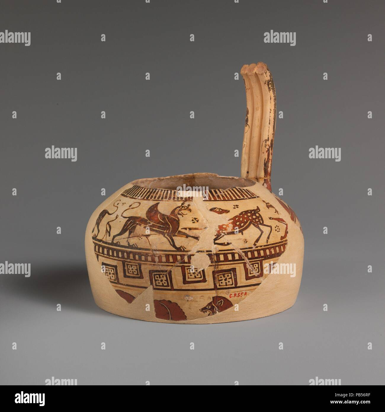 Fragment of a terracotta oinochoe (jug). Culture: East Greek, Milesian, Fikellura. Dimensions: H. of a 5 3/4 in. (14.6 cm); length of b 3 1/2 in. (8.9 cm). Date: ca. 560-550 B.C..  On the shoulder, deer attacked by sphinxes and griffins, water birds  On the body, bull attacked by lion  This fine fragment represents an early phase in the development of Fikellura pottery. In the animal groups as well as the drawing, there is a vitality that later subsides. The name Fikellura derives from a site on the island of Rhodes to which this fabric has been attributed. It is now established that the cente Stock Photo