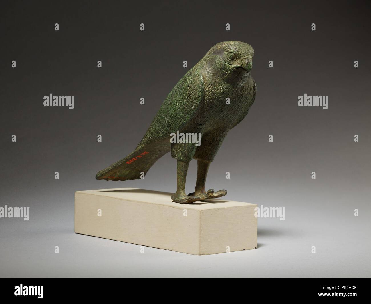 Falcon. Dimensions: H. 8.9 cm (3 1/2 in.); W. 5 cm (1 15/16 in.); L. 12 cm (4 3/4 in.). Date: 664-30 B.C..  The falcon stands with his wings swept back. The figure has beautifully rendered facial markings and short and long feathers all over the body. The tail extends back behind the bird in a single long, clean line. The falcon could be a standalone offering but it is very likely that it once stood on a mummy box, which would have housed a falcon mummy. Such falcon mummy boxes, or sarcophagi, would have been offered for deposition in animal necropoleis, not just in relation to the cult of the - Stock Image