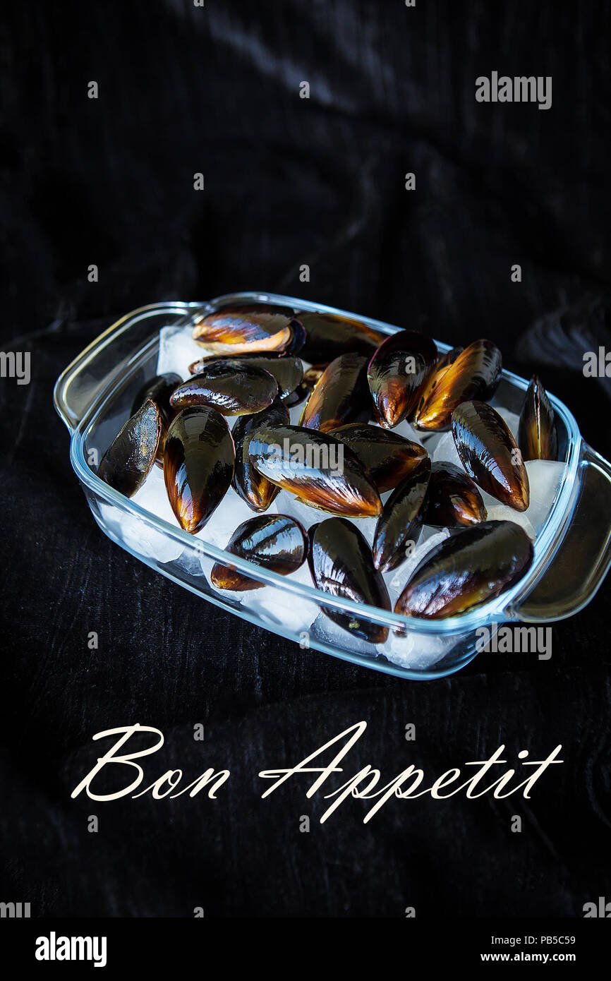 Very tasty and fresh mussels on ice cubes-the inscription of a Bon Appetit. - Stock Image