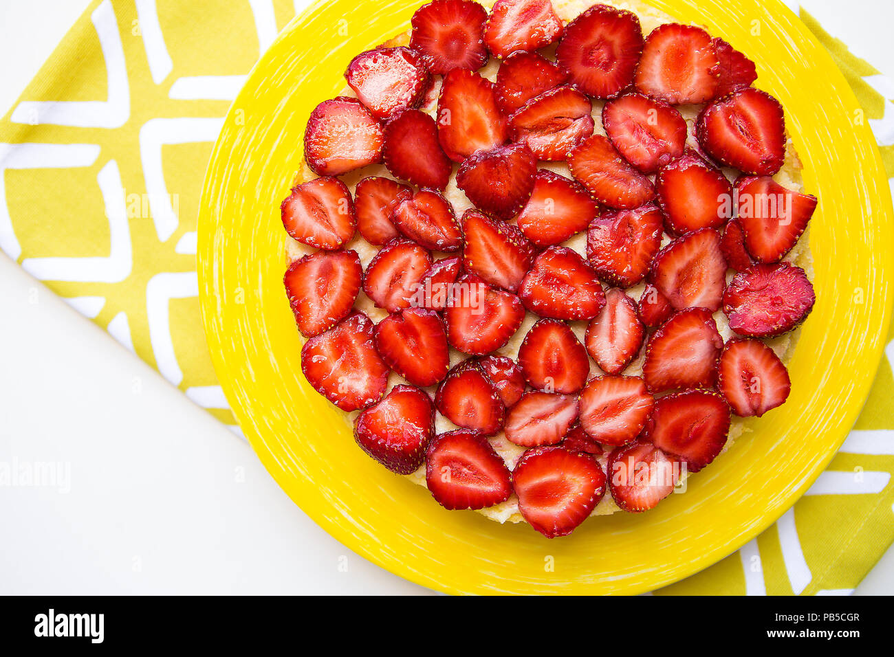 Beautiful and delicious strawberry cake stands on a yellow napkin - Stock Image