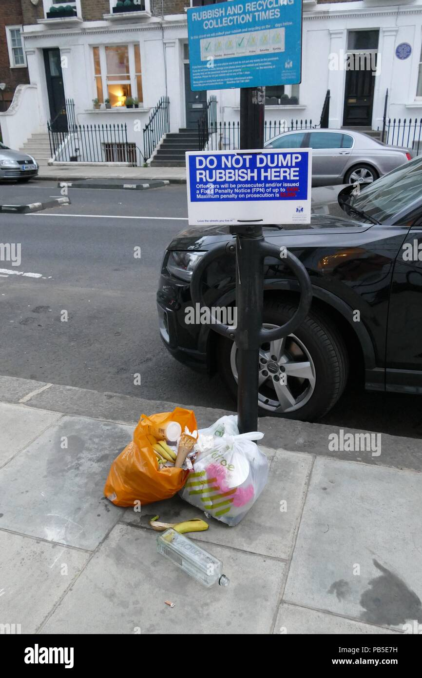 bags of rubbish left on pavement on London street - Stock Image