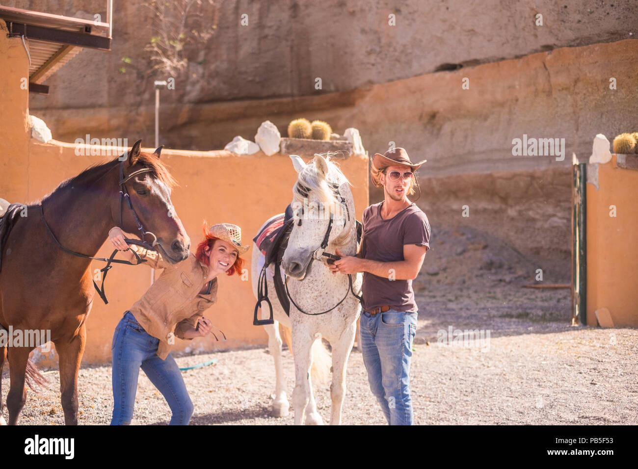 two horses and two caucasian young man and woman couple ready to ride and enjoy the sunny day. natural and alternative lifestyle to enjoy nature and a - Stock Image