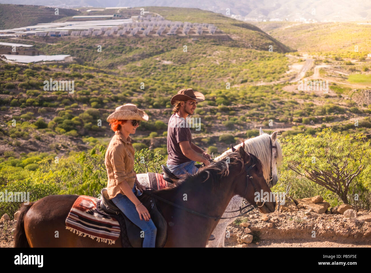 couple of rider man and woman with brown and white horses go and enjoy the outdoor leisure activity in excursion traveling the mountains. modern cowbo - Stock Image