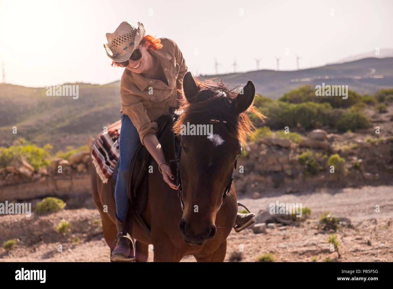 cheerful red hair lady ride a beautiful brown horse in friendship and enjoy the outdoor day together. relationship and pet therapy. happy and joy life - Stock Image