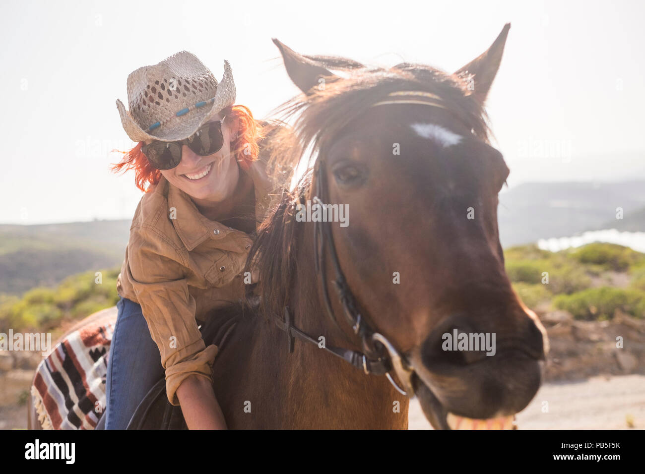 beautiful cheerful young woman enjoy and ride her brown cute horse in friendship and relationship. animal lover and pet therapy concept. travel and va - Stock Image