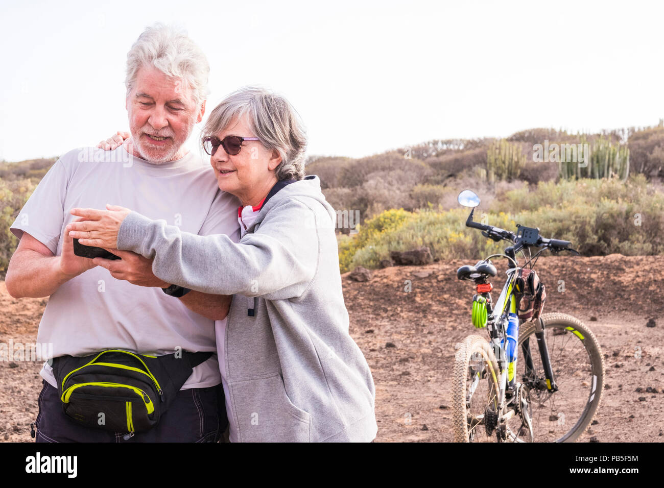 couple of beautiful caucasian active adult senior enjoy mountain bike. old and young rider in outdoor sport bikes activity together checking the gps m - Stock Image