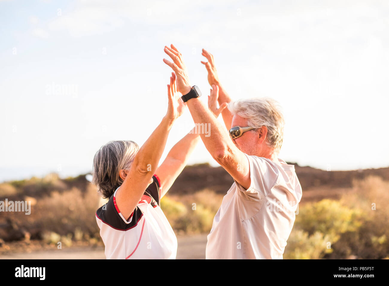 senior mature couple enjoy and win together giving five and hugging under a nice weather day of sun in summer. sport activity and clothes. Active aged - Stock Image