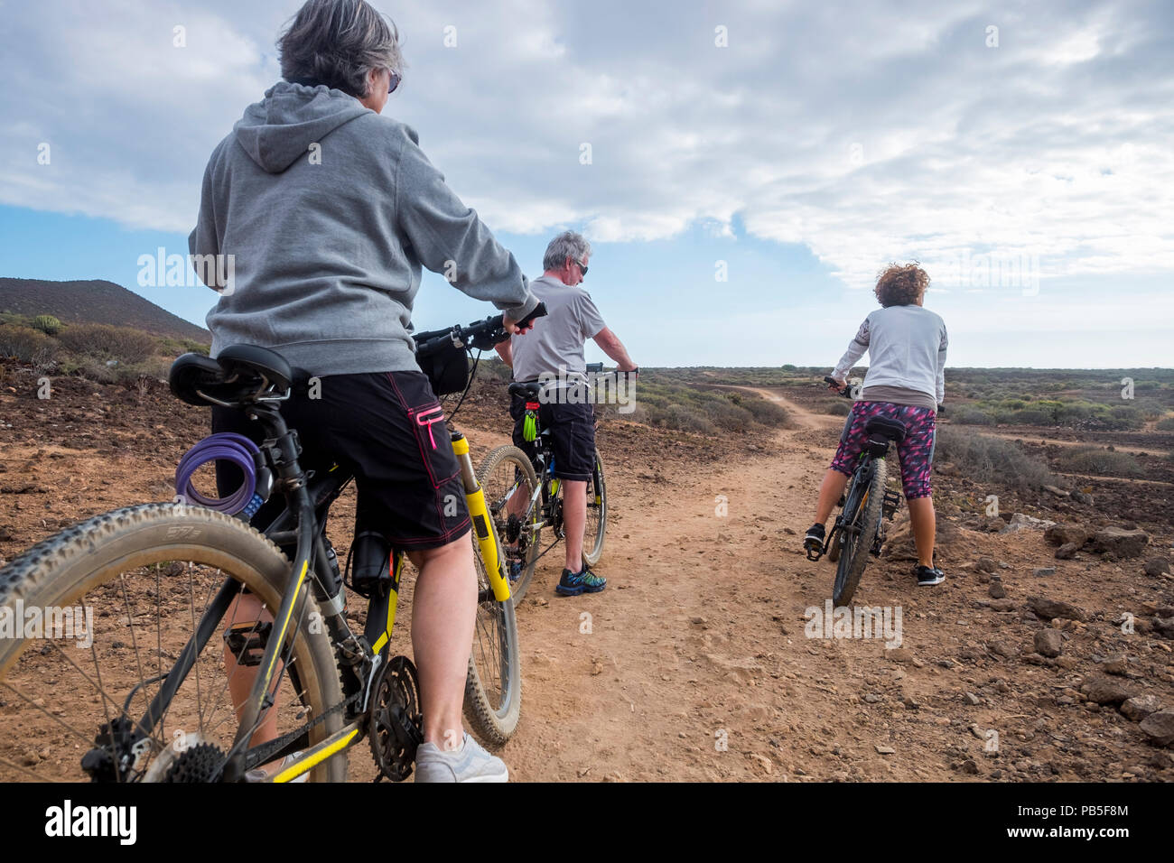 group of ciclyst with mountina bikes riding on the desert in tropical island and enjoying the leisure outdoor sport activty to stay health and nice. b - Stock Image